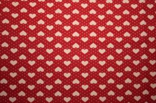 Tissu : petits coeurs taupe sur fond rouge foncé
